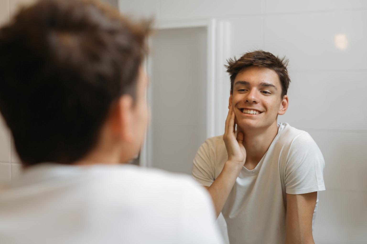 鏡で肌の状態をチェックする男性